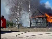 Под Великим Новгородом догорает дом. По сухой траве огонь может добраться до соседей